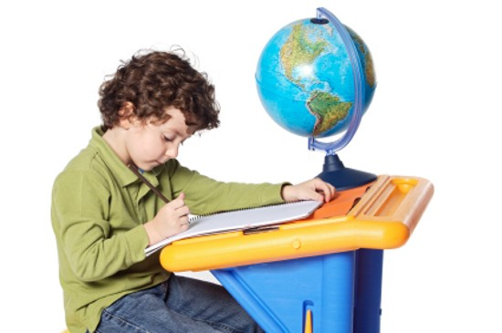 a child studying in front of a globe
